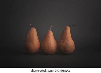Three bosc pears on dark background