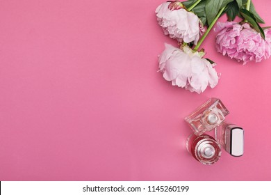 three bottle of female perfume and bouquet of peony flowers on pink background. top view