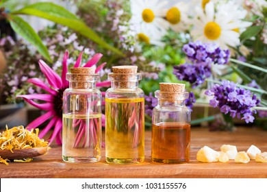 Three bottles of essential oil with frankincense, lavender, echinacea, chamomile and other herbs and flowers in the background