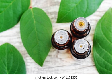 Three bottles of essential oil over wooden background. Top view, copy space.