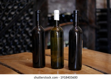 Three bottles of homemade white wine, without a label, on the wooden table in the wine cellar
