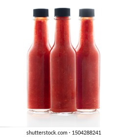 Three bottles of hot sauce without lables isolated on a white background.
