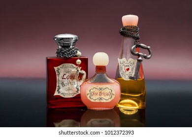 Three bottles with love potion on dark blue surface