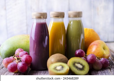 Three bottles with smoothies and fresh fruit (apple, grapes, kiwifruit, mango)