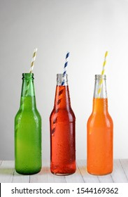 Three bottles of soda with Straws on a wood table, Lemon-Lime, Strawberry and Orange flavors.