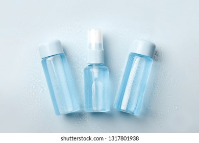 Three  bottles of tonic or lotion sprinkled with water on blue background. Freshness and body care. Female cosmetics. Micellar water. Travel set of face care cosmetic