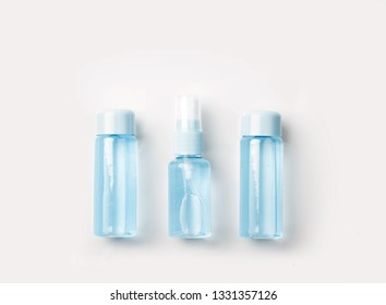Three  bottles of tonic or lotion sprinkled with water on pink or white background. Freshness and body care. Female cosmetics. Micellar water. Travel set of face care cosmetic