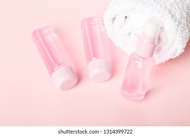 Three  bottles of tonic or lotion and white towel on pink or powder background. Freshness and body care. Female cosmetics. Micellar water. Travel set of face care cosmetic