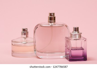 Three bottles with women perfume in a pink background. Women products.