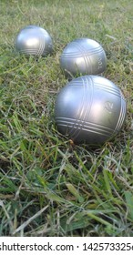 Three boules balls are on the field. The balls are suitable for tournaments.