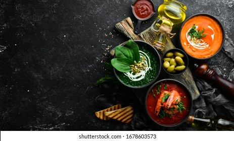Three bowls with colored soup. Spinach, tomato and carrot soup. Healthy food. On a dark background.
