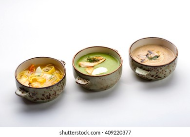 Three bowls with different soups: chicken fillet noodles soup, cream of broccoli soup with turkey and cream cheese, wild mushrooms soup.