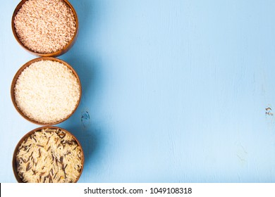 Three bowls with different varieties of rice on a wooden background, top view. Ingredient for a healthy diet.