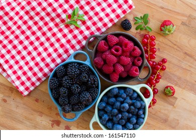 Three bowls of fresh raspberry , bluberry and black berry on wooden table