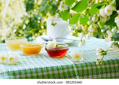 Three bowls of honey and cup of tea on a table under a bush of jasmine. Summer tea drinking
