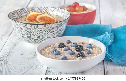 Three bowls of oatmeal with different berry and fruit toppings: top view