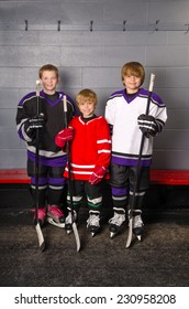 Three Boy Hockey Players are dressed in their gear in change room of arena