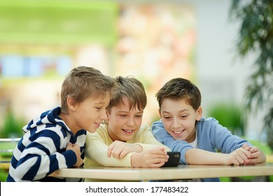 Three boys absorbed in smartphone screen