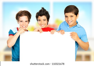 Three boys in classroom holding white clean board, happy children enjoying studying at school, smiling teenager having fun indoors, back to school, best friends concept, love to education