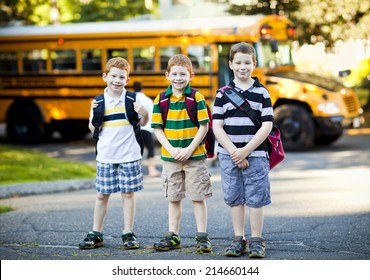 Three boys in front of a school bus