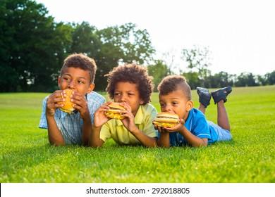 Three boys are having breakfast and tasting hamburger on the sunny glade.