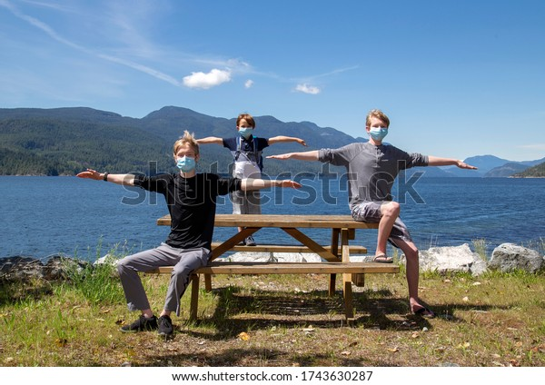 Three boys at a picnic table in a park showing physical distancing and wearing face masks.
