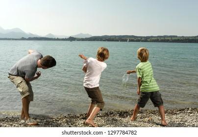 Three boys playing outdoors skimming stones across lake