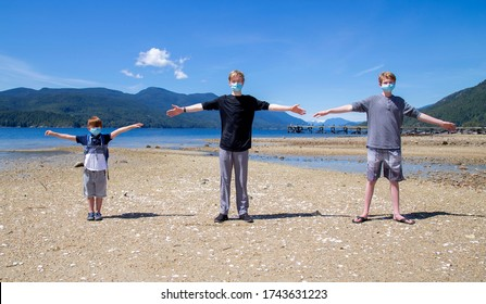 Three boys standing at a beach park with arms outstretched showing the two meter social distancing while wearing face masks.