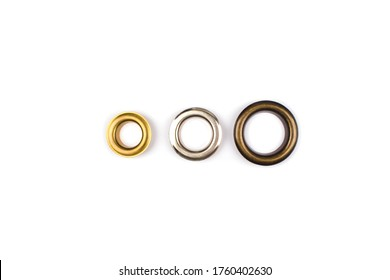 Three brass multicoloured metal eyelets or rivets - curtains rings for fastening fabric to the cornice, isolated on white with copyspace for text for your presentation