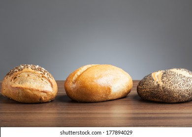Three bread rolls (regular, caraway, poppy seed) side by side on table.