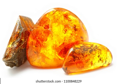 Three bright pieces of amber of different shapes and colors on a white background. Amber texture. A natural mineral for jewelry. Frozen resin with inclusions insects inside. Sunstone