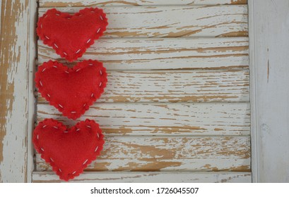 Three bright red felt hearts with white stitching on worn wood shutter with white peeling paint.