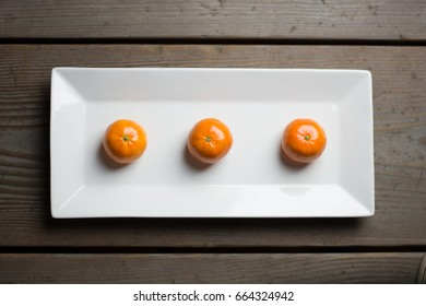 Three brightly colored mandarin oranges aligned on a white plate