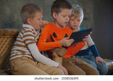 Three brothers in bright clothes are playing on a tablet