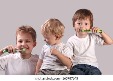 three brothers brushing teeth together