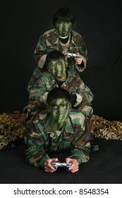 Three brothers in camo paint and fatigues playing video games.