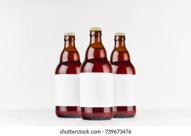 Three brown belgian steinie beer bottles 500ml with blank white label on white wooden board, mock up. Template for advertising, design, branding identity.