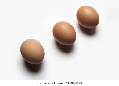 Three brown brown eggs photographed on a white surface