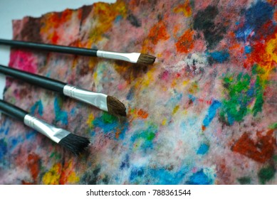 three brushes at watercolor spots in wet wipe