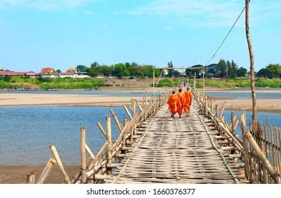 Three buddhist monks on bamboo bridge across Mekong river between Kampong Cham city and island of Koh Paen, Cambodia