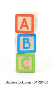 three building blocks with alphabets on white