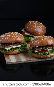 three burger with fried mushrooms, cheese, tomato and salad leaves on wooden board, place for text