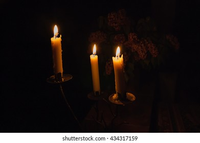 Three burning candles in chandelier and Lilac bouquet in ceramic jug. Romantic night.