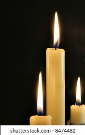 Three burning candles close-up over black background