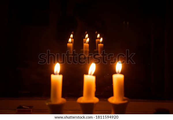 Three burning candles in multiple reflections. Flame of a candle on a dark background. Selective focus