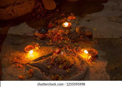 Three burning candles near the ancient altar with flowers at night time on Diwali