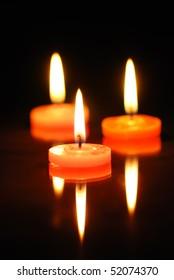 Three burning candles on black background