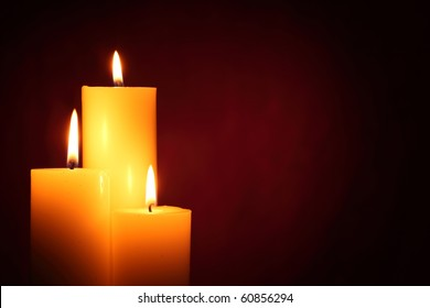 Three burning candles on red background