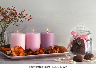 Three burning candles on stand with dry decorative flowers and bark. Pearl necklace, jar for cookies and two cookies in form of heart lay on light gray background.