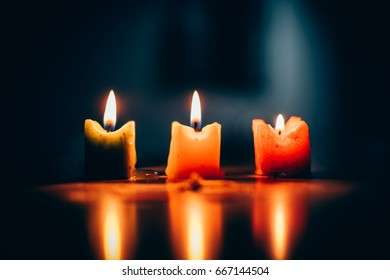 Three burning candles in a row with dark green background or aura. May represent lights during the dark times in life. Selective focus.